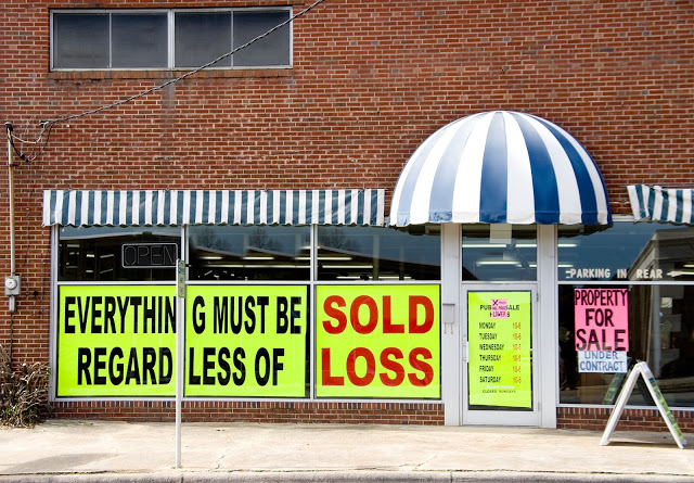 Everything must go sign in store window, going out of business, dissolving a corporation